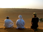 Sitting together, peacefully watching the sunset in the Wahiba Sands Desert with our Omani Bedouin guides and their camp in the distance. This picture captures the hospitality and tranquility of Oman despite its location in the tumultuous Middle East.